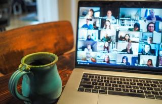 A laptop with a zoom meeting is open with a coffee cup beside.