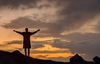 Silhouette of a woman standing on a hill with her arms stretched out, sunset in the background.