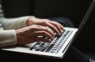 Woman's hands poised over a laptop.