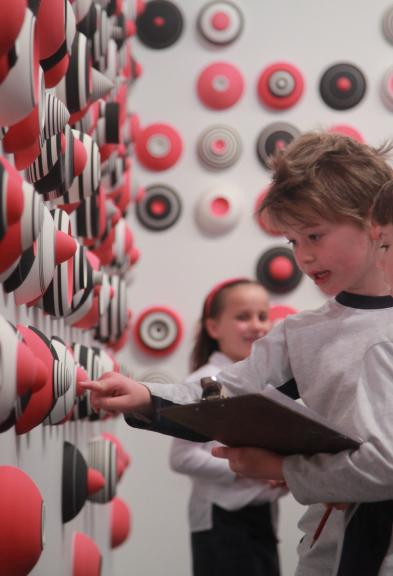 Two young children examine an artwork of black, white and red spheres attached to a wall.