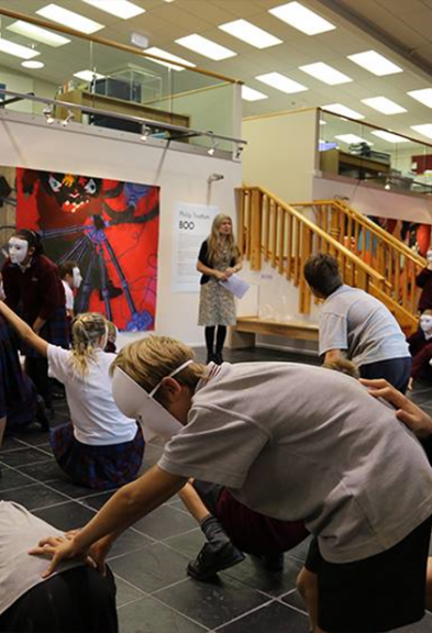 Teenage students in uniform, wearing scary masks act out an activity in an art gallery foyer.