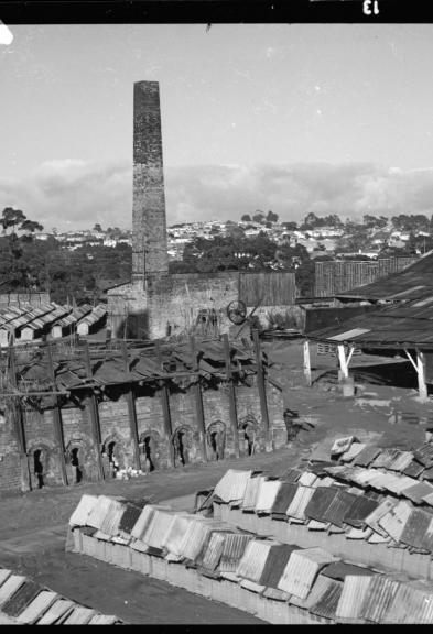 Black and white photo of old brickworks brick yard and kiln in background.