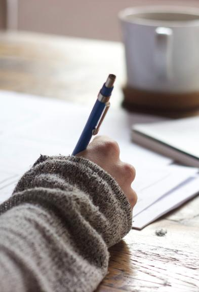 Close up of a person at a desk writing a letter, coffee cup in the background.