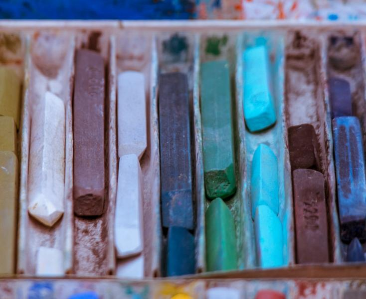 Box of pastels of varying colours, arranged horizontally.