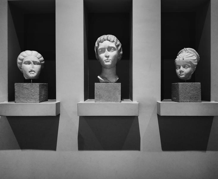 Three sculpture heads sitting on floating stone shelves