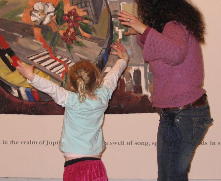 Young child and woman standing facing an artwork, acting out what they see in the image.
