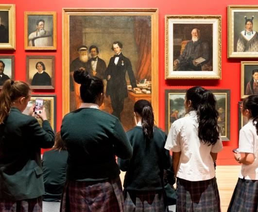Group of school girls looking at portraits hanging on an orange wall.